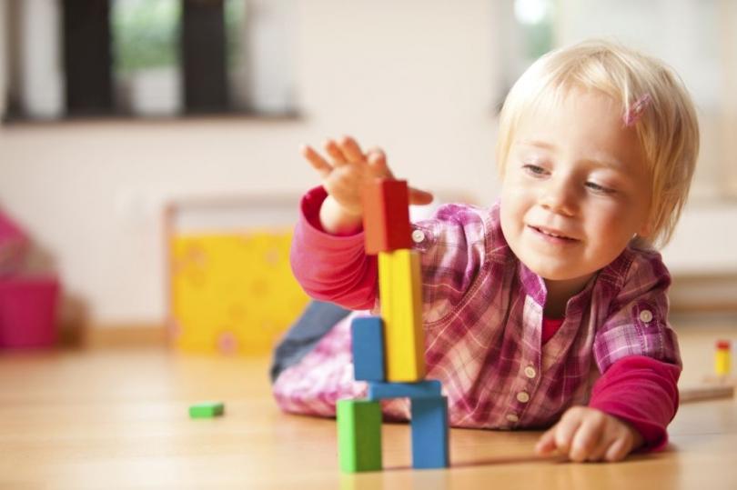 Dziecko bawiące się drewnianymi klockami