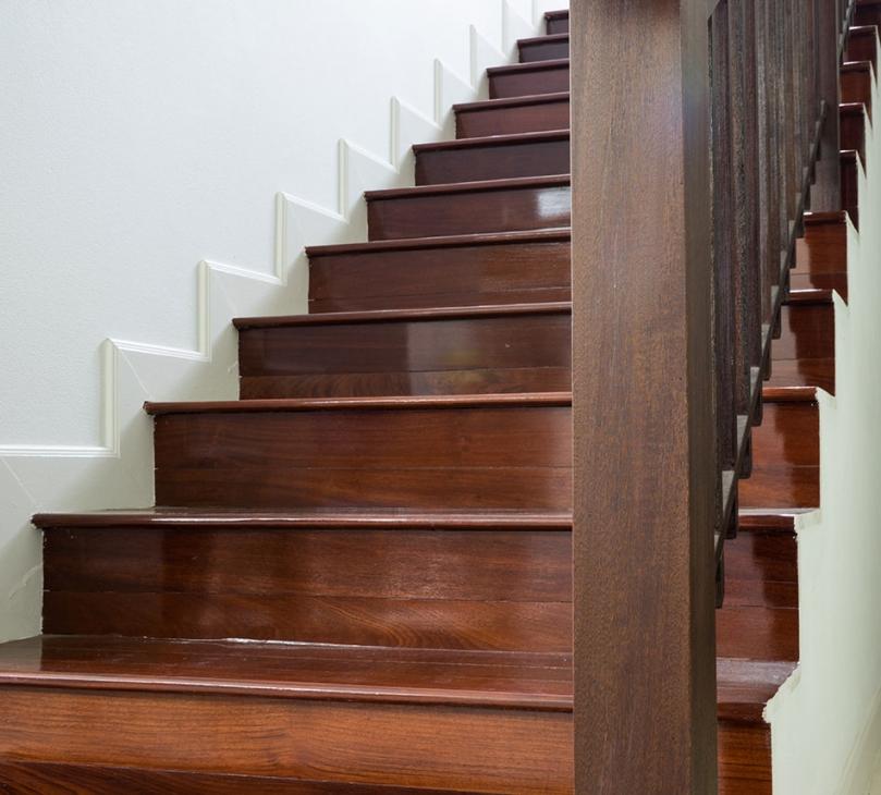 Ciemne drewniane schody ibiałe ściany