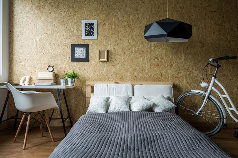 Płyta OSB na ścianie za łóżkiem