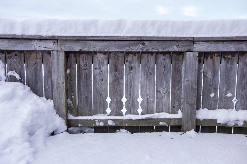 Drewniany płot pokryty śniegiem