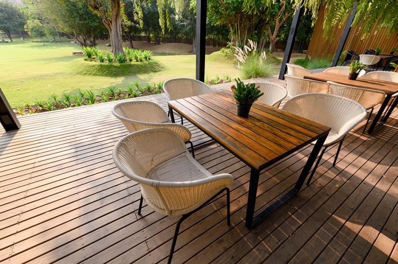Przestronny drewniany taras ze stolikami