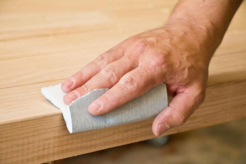 Przecieranie drewnianej powierzchni papierem ściernym